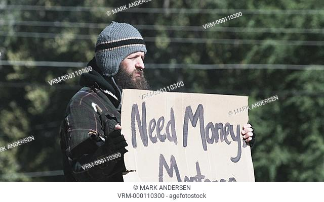 homeless man holding a sign for money
