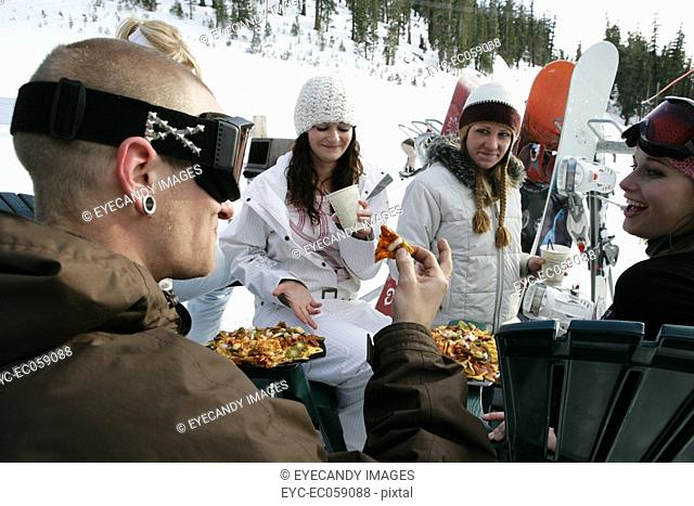 Group of friends eating and drinking at a ski resort