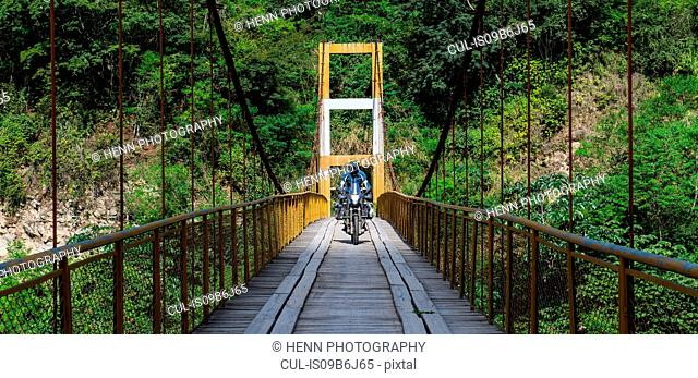 Man driving touring motorbike on suspension bridge over the Urubamba river, Santa Teresa de Molinos, Huancavelica, Peru, South America