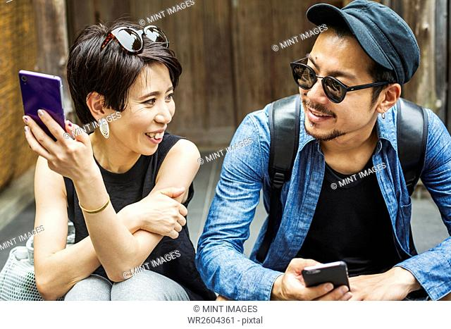 A couple seated side by side holding their smart phones, looking at each other