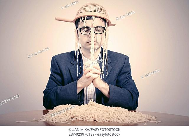 Pastafarian wearing a colander praying for pasta to the Flying Spaghetti Monster