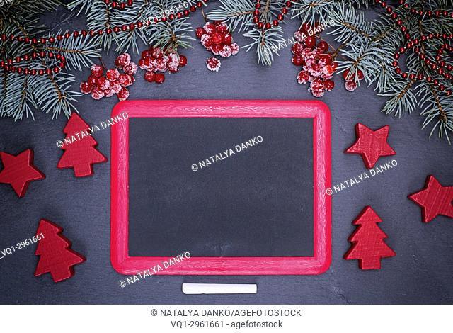 empty black frame and a piece of chalk on a black background, near a festive decoration