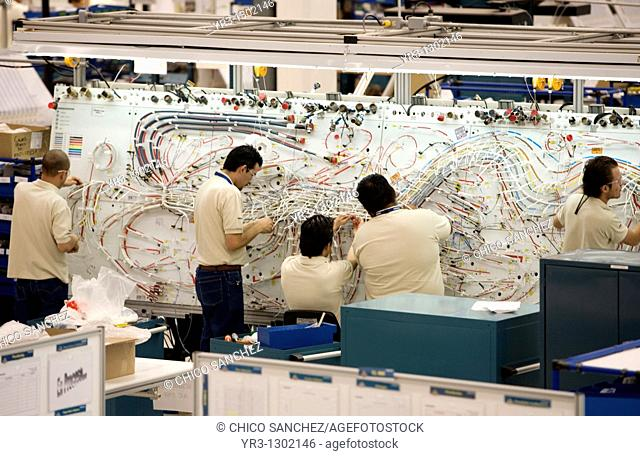 Workers build the electronic system of a plane in a Bombardier Aerospace plant in Queretaro, Mexico, March 2, 2008