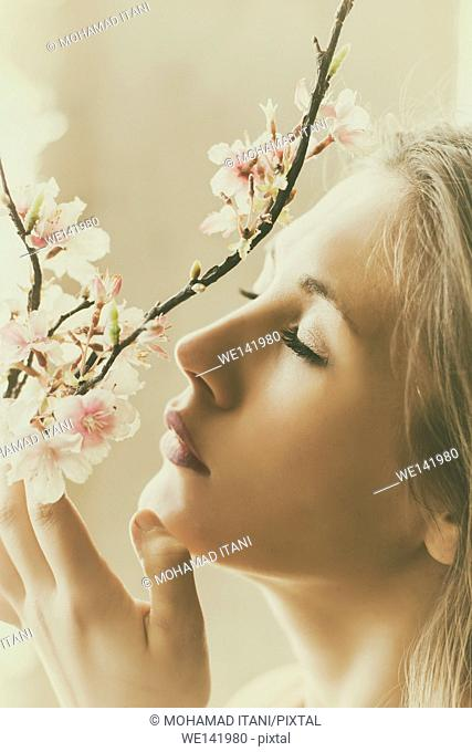 Beautiful young woman smelling flowers on the tree