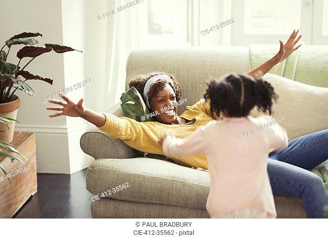 Enthusiastic mother on sofa greeting running daughter