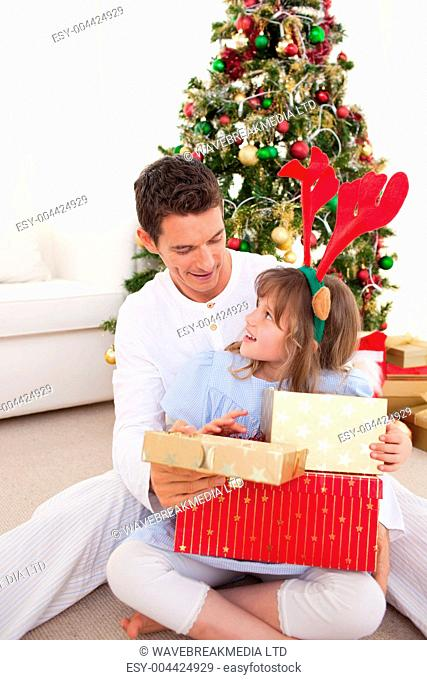 Smiling father and his daughter opening Christmas gifts