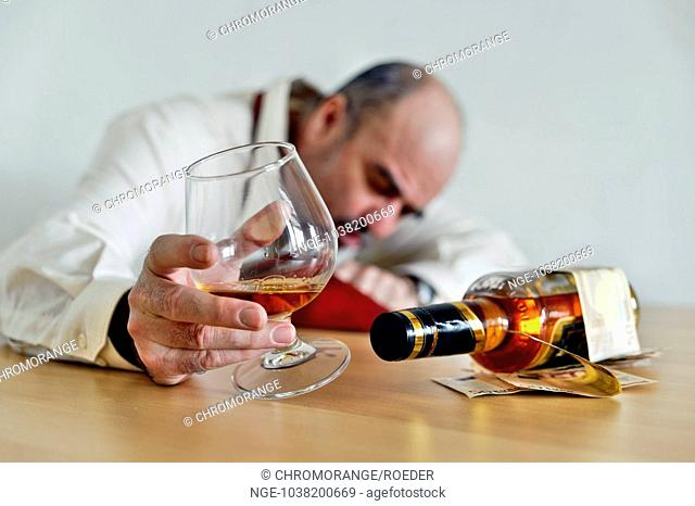 Alcoholic sitting with a cognac and a bottle of brandy at the table