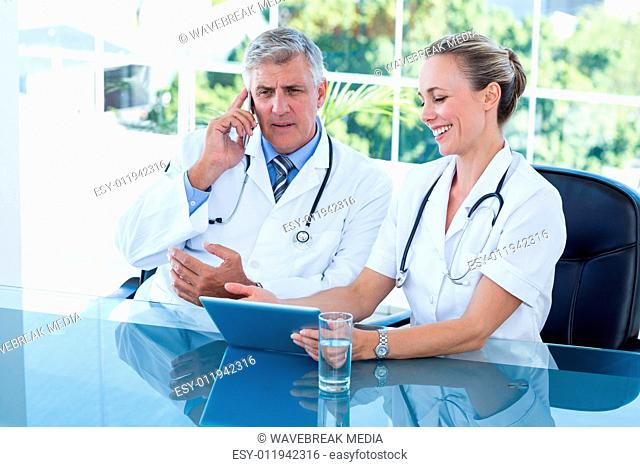 Smiling doctors working together on tablet