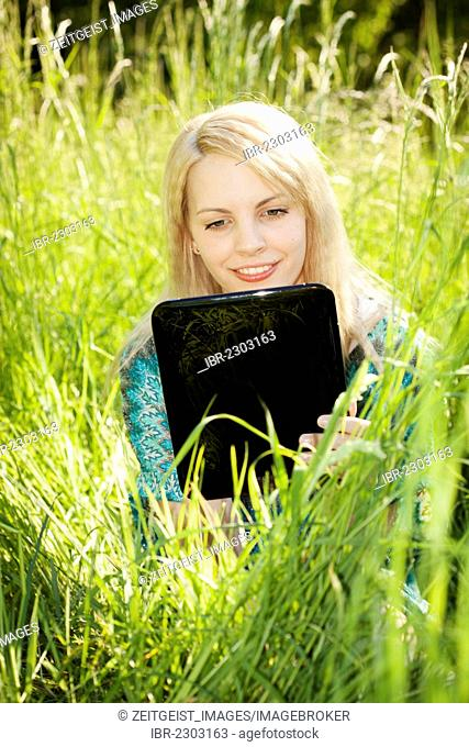 Young woman sitting in tall grass on a meadow working on a tablet PC, computer