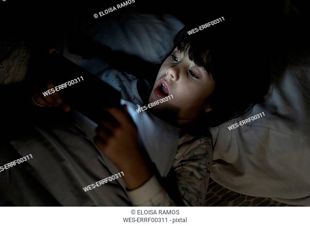 Shocked girl lying in bed using smartphone at night