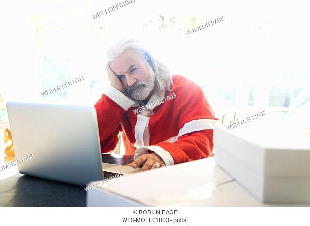 Frustrated Santa using laptop at home
