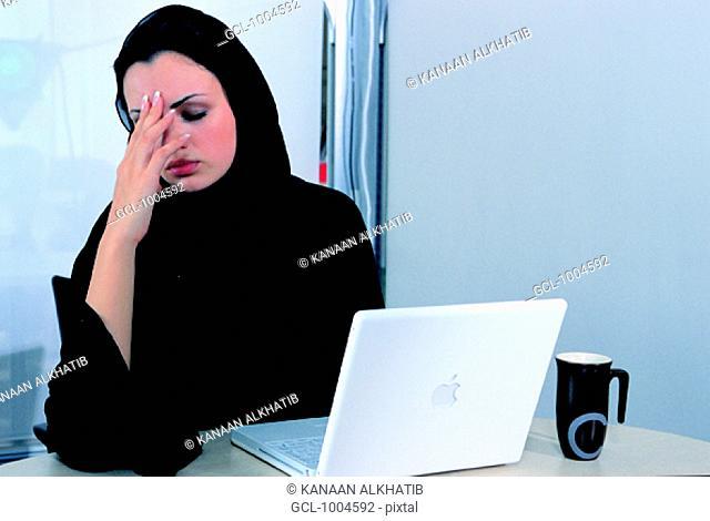 Arab businesswoman holding her head