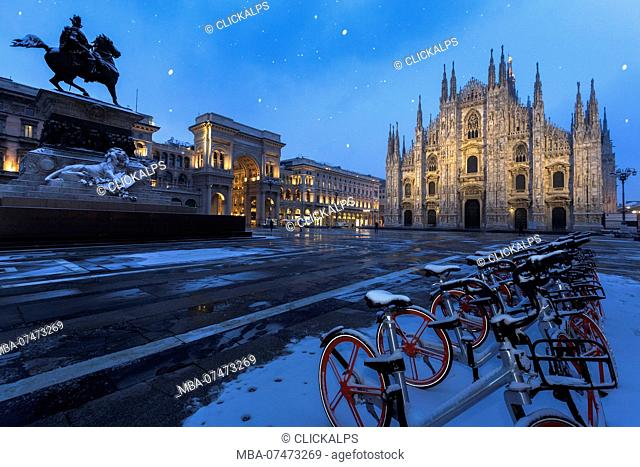 Bicycles parked in PIazza Duomo during snowfall at dusk, Milan, Lombardy, Northern Italy, Italy