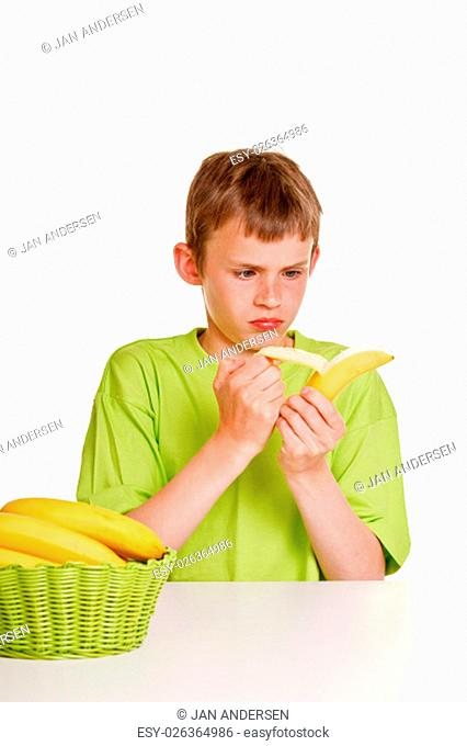 Young boy peeling a banana with an expression of distaste and a scowl as he sits at a table with a basket of fresh fruit