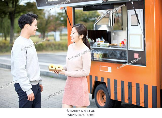 Smiling man and woman near food truck