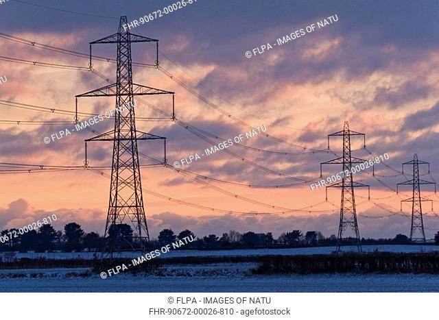 Electricity transmission pylons and overhead wires, crossing over snow covered farmland at sunset, Dorset, England, december