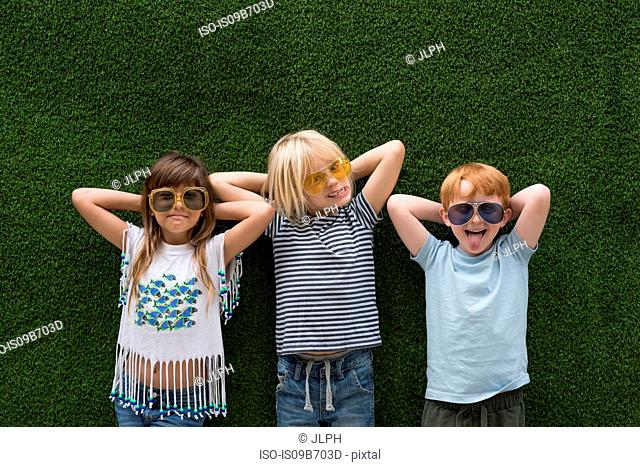 Children in front of artificial turf wall, hand behind head wearing sunglasses