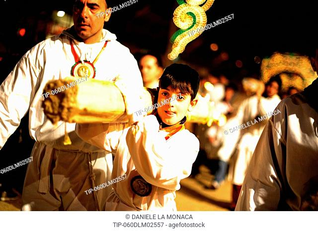 Italy, Sicily, Catania, men carrying with candles during Sant'Agata Feast the Patron Saint of the city