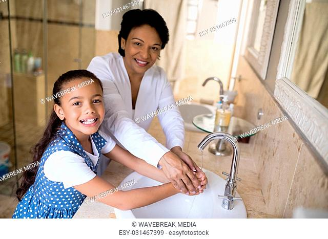 Portrait of grandmother and granddaughter washing hands