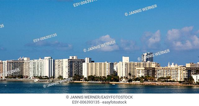 Row of nondescript apartment buildings by the water in Miami, FL, USA