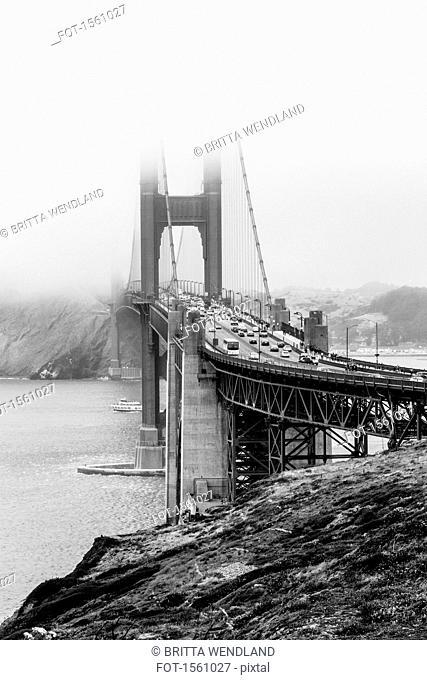 Golden Gate Bridge over Bay against mountain during foggy weather, San Francisco, California, USA