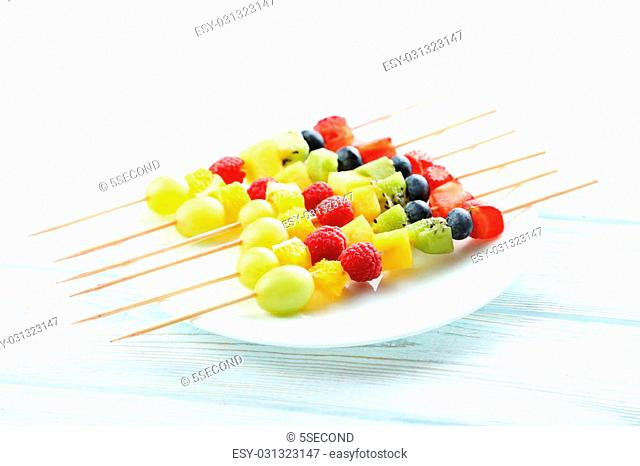 Fresh fruit on skewers on a white wooden table