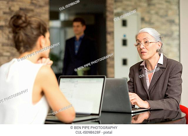 Mature businesswoman and female colleague having discussion over office desk