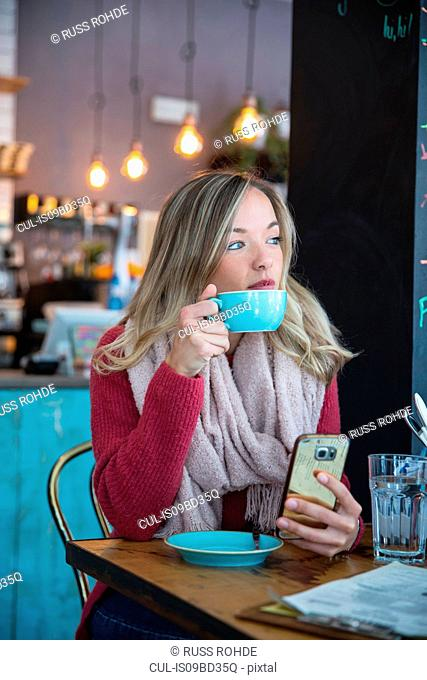 Woman sitting in cafe, holding smartphone, drinking coffee