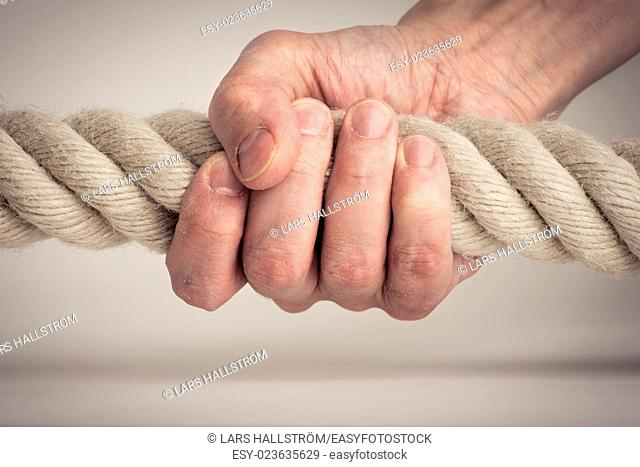 Hand holding nautical rope in close-up. Symbol of power, strength and effort
