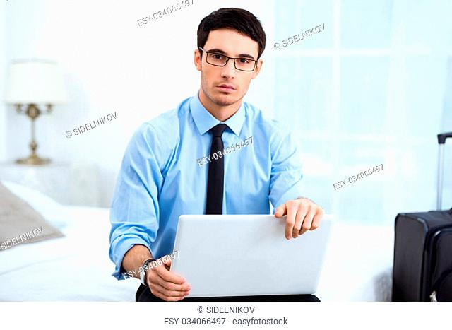 Young businessman looking at camera and using laptop while sitting in cozy hotel room with suitcase