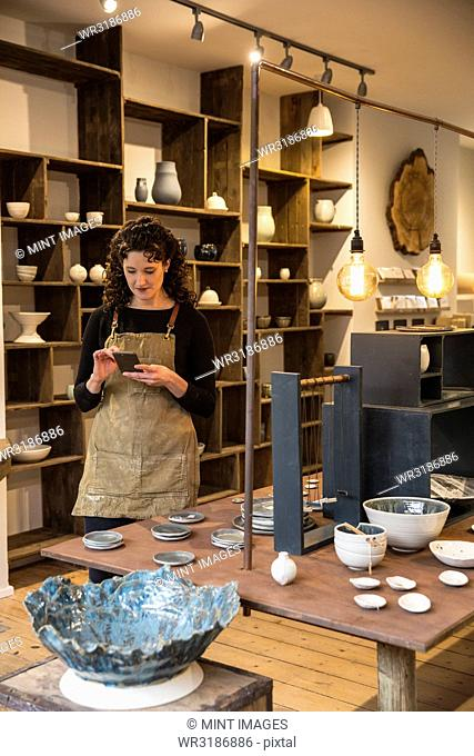 Woman with curly brown hair wearing apron standing in her pottery shop, looking at mobile phone