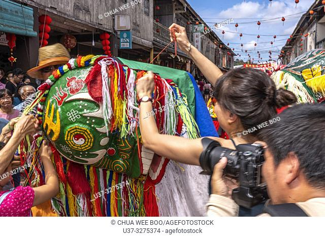 People pull the lion head's hair in belief of getting good fortune during the Chinese New Year Festival Capgomeh year 2019 15th day of the 1st month at Siniawan