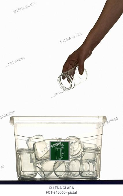 A human hand throwing a glass jar in a recycling bin