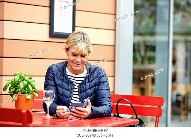 Mature woman reading smartphone texts at sidewalk cafe