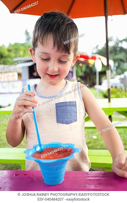 Lifestyle portrait of a young five year old child eating shave ice in Oahu Hawaii at a food truck