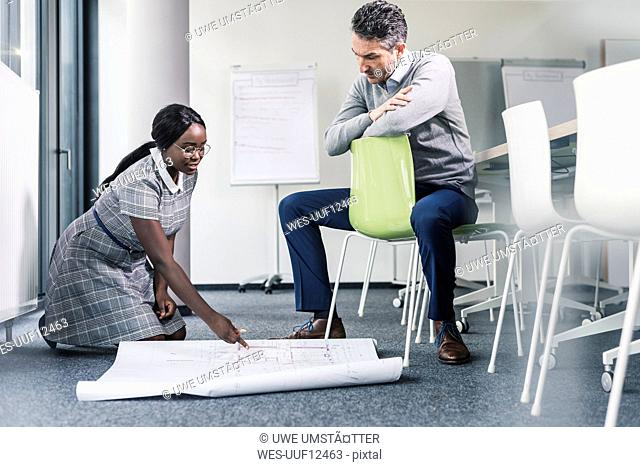 Colleagues working on plan in office conference room