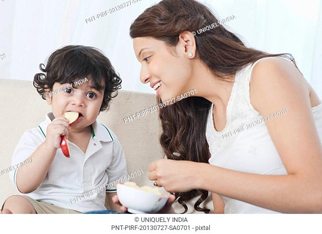 Woman feeding apple to her son