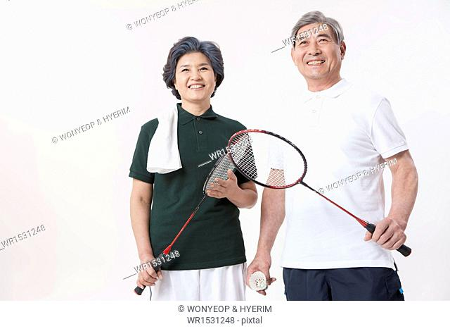 an old couple posing with badminton gear