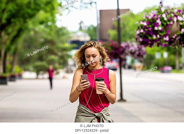 A young woman walking down a street near a university campus texting on her smart phone; Edmonton, Alberta, Canada