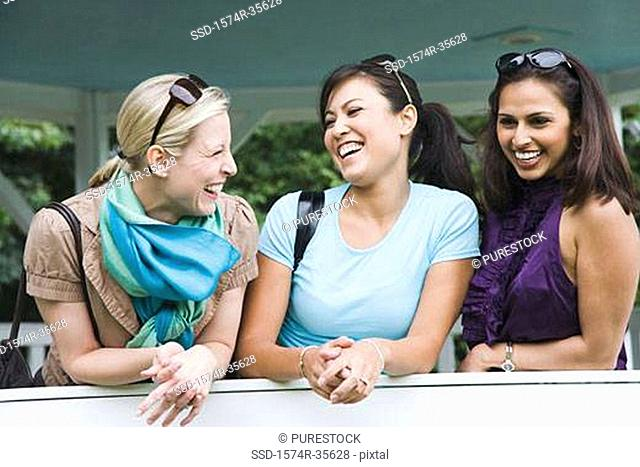 Three women leaning against wall and smiling