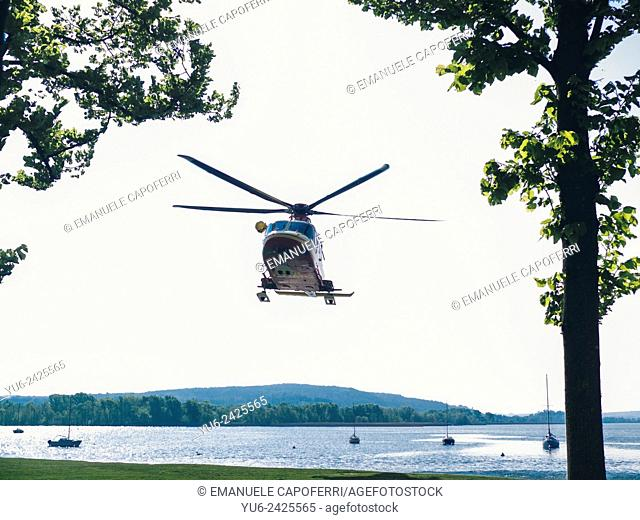 While helicopter takes off from the lake shore, Angera, Varese, Lombardy, Italy