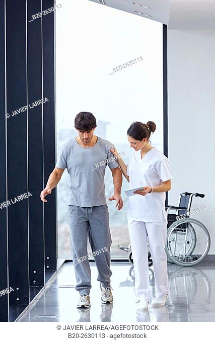 Physical therapist helping a patient to walk