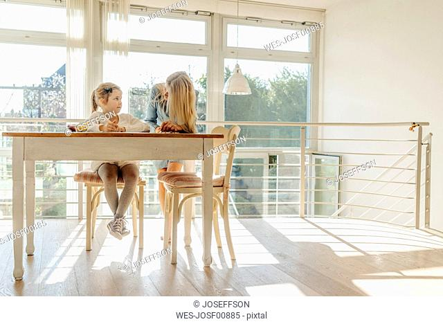 Mature woman and girl at home at the table