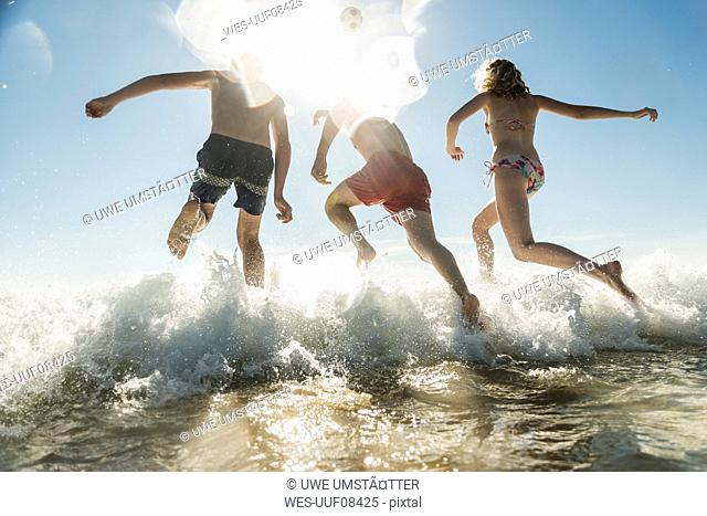 Friends jumping into the sea