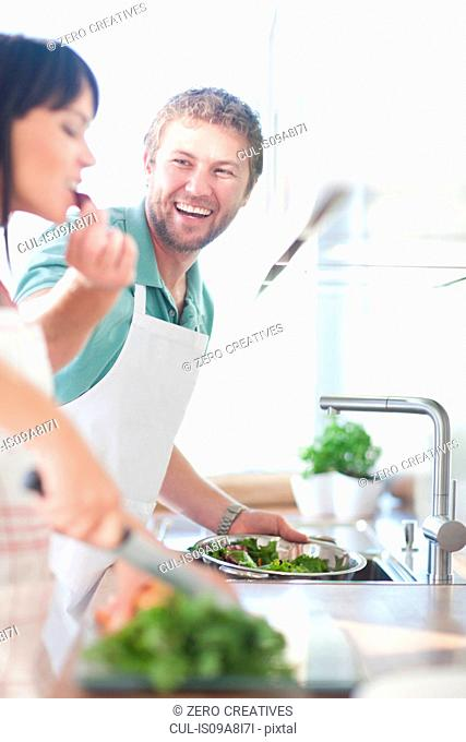 Couple preparing food, man feeding woman
