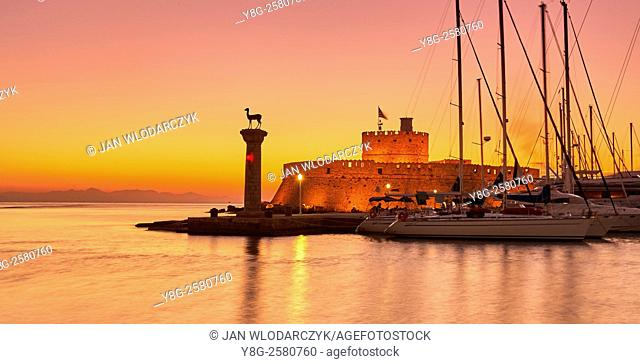 Mandraki harbour and fortress Agios Nicolaos before sunrise, Rhodes town, Rhodes Island, Greece, UNESCO