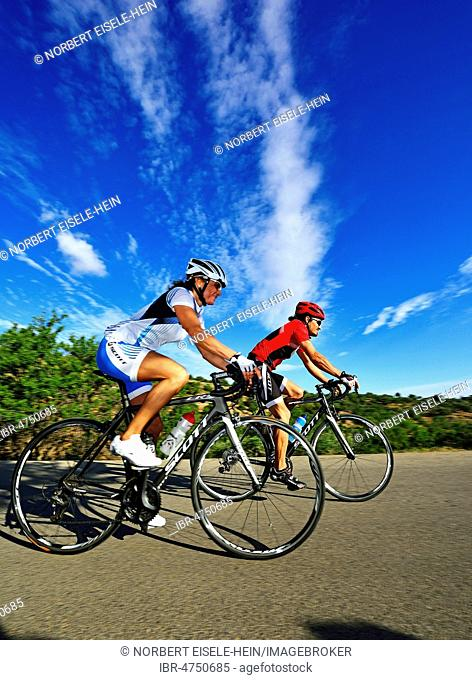 Two racing cyclists on the road, near Kalamafka, Crete, Greece