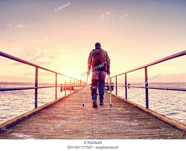 Hurt man with hooded jacket and forearm crutches standing on sea bridge within early morning and thinking. Gloomy nostalgic silhouette of sad lonely melancholic...