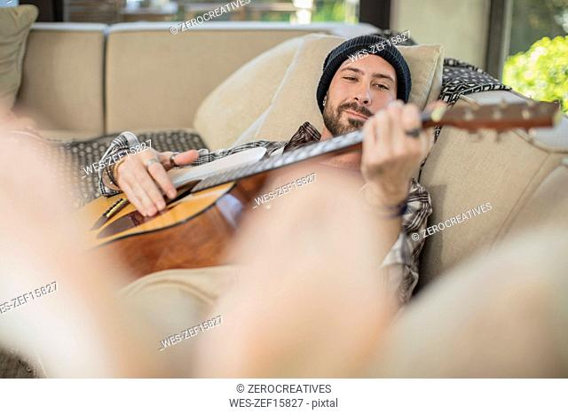 Young man at home lying on couch playing guitar