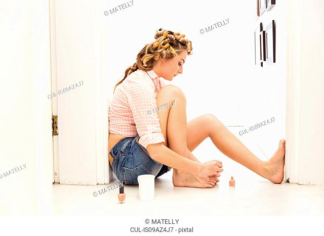 Young woman, foam rollers in hair, painting toenails
